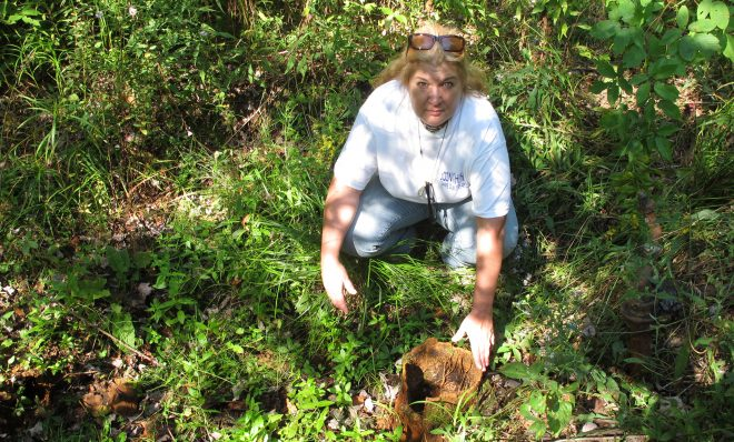 In this 2012 photo, Laurie Barr points to an abandoned well near the Allegheny National Forest.