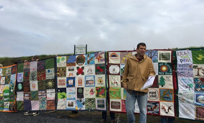 Mark Clatterbuck stands in front of a quilt designed to protest the Atlantic Sunrise pipeline.