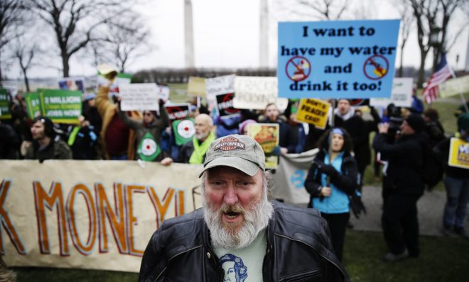 Fracking opponents, including Ray Kemble of Dimock, Pa., front, demonstrate before Governor-elect Tom Wolf takes the oath of office to become the 47th governor of Pennsylvania, Tuesday, Jan. 20, 2015, at the state Capitol.
