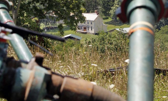 This July 27, 2011 file photo shows a farmhouse in the background framed by pipes connecting pumps where the hydraulic fracturing process in the Marcellus Shale was underway at a Range Resources site in Claysville, Pa.