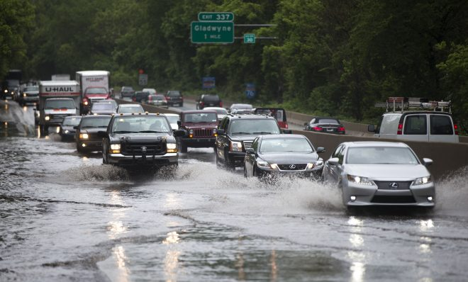 In this 2014 photo, vehicles pass through a flooded section of eastbound Interstate 76 near the Gladwyne exit. Climate scientists say the Pennsylvania can expect more precipitation as global warming continues.