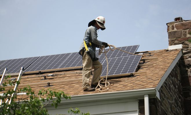 In this photo from May 2017, Patrick Whittaker of Solar States installs solar panels on the roof of a home in Bryn Mawr, Pa.