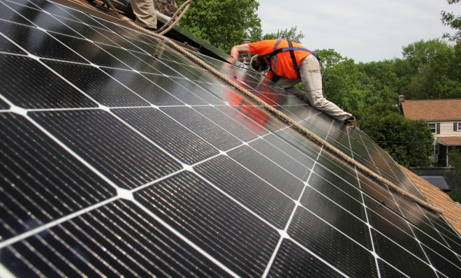 Dennis Hajnik installs solar panels on a roof in Bryn Mawr.