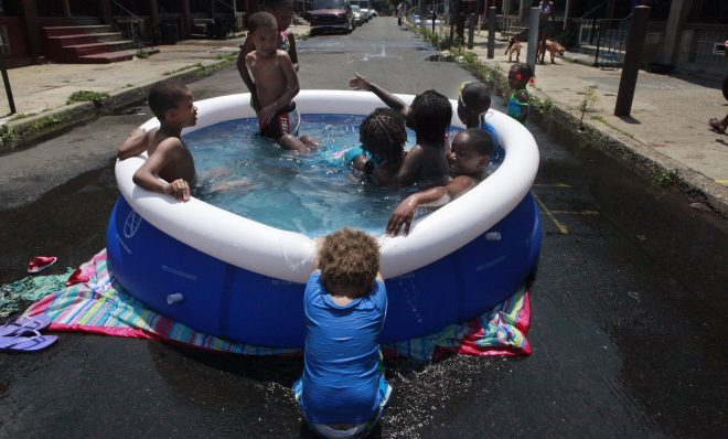 In this June 2012 photo, Michael Hall, 2, pulls down the edge of the pool while others swim  in Philadelphia. Climate change has already brought hotter weather to the state, where some areas have warmed 2 degrees in 30 years.