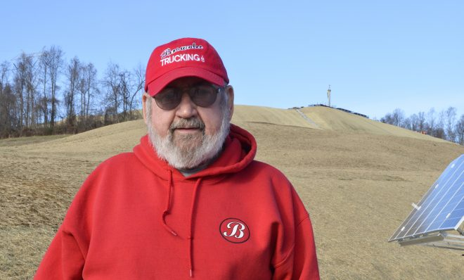 Washington County resident Frank Brownlee stands in his backyard, where a rig on the hill behind him is drilling natural gas wells.