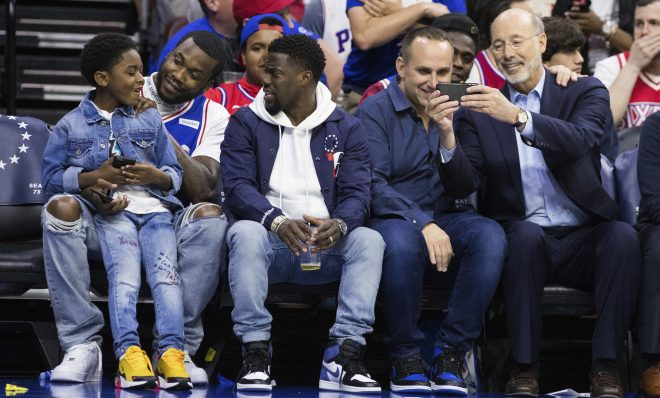 Rapper Meek Mill, center left, looks on with his son, left, and actor Kevin Hart, center, as 76ers' co-owner Michael Rubin, center right, looks at Pennsylvania Gov. Tom Wolf's phone, right, during the first half in Game 5 of a first-round NBA basketball playoff series between the Miami Heat and the Philadelphia 76ers, Tuesday, April 24, 2018, in Philadelphia. The 76ers won 104-91. (AP Photo/Chris Szagola)