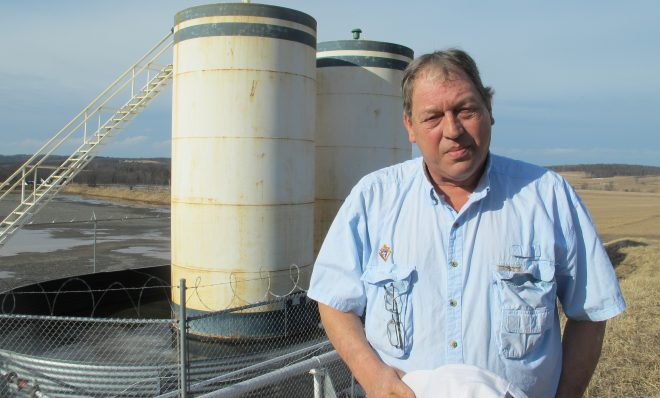 Jim Barrett stands next to a wellpad on his farm in Bradford County. He says Chesapeake Energy, which drilled four natural gas wells on his land, is cheating him out of royalty money.