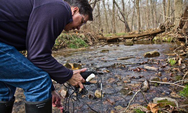 John Jackson, senior research scientist at the Stroud Water Research Center, measure conductivity in the White Clay Creek stream.