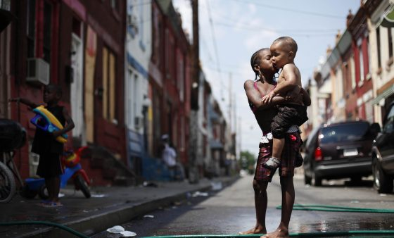 File photo. Aniyah Davis kisses her cousin William Respes as they play in water from a garden hose during a July 2011 heat wave in Philadelphia. The city has a pilot project to help neighborhoods with vulnerable populations adapt to rising temperatures.