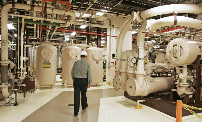 In this Feb. 25, 2010, file photo, an Exelon Corp. employee walks past equipment in the turbine building at the Oyster Creek Generating Station, a nuclear power plant in Lacey Township, N.J. Shutting down the site of the nation's oldest nuclear power plant will take 60 years and cost $1.4 billion, according to a plan filed May 21, 2018, by a subsidiary of Chicago-based Exelon Corp. and under review by the Nuclear Regulatory Commission.