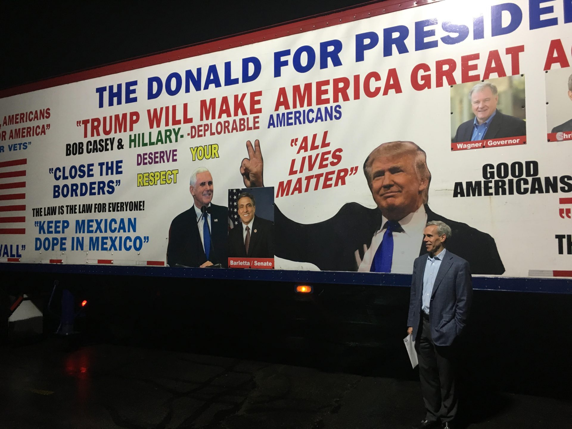 Republican congressional candidate John Chrin poses for a picture in front of a Donald Trump-themed tractor-trailer on Sept. 12, 2018 in Luzerne County.