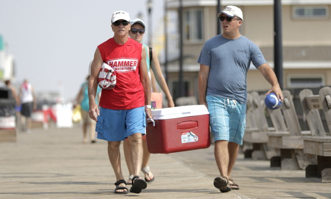 People carry a cooler while strolling at the boardwalk on their way to a beach spot at the New Jersey shore, Friday, Aug. 17, 2018, in Seaside Heights, N.J.