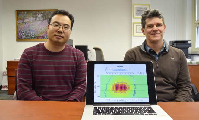 Tieyuan Zhu, left, and Eugene Morgan of Pennsylvania State University are part of a research team studying carbon storage. They are pictured here with a model that helps explain how carbon dioxide moves through rock underground.