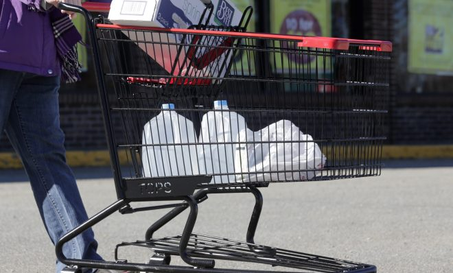 In this Friday, Feb. 26, 2016 photo, a woman leaves a Tops supermarket with bottled water that is being supplied to residents in Hoosick Falls, N.Y. PFOA, long used in the manufacuring of Teflon pans, Gore-Tex jackets, ski wax, and many other products has turned up in the water in factory towns around the country like Hoosick Falls, impacting drinking water.