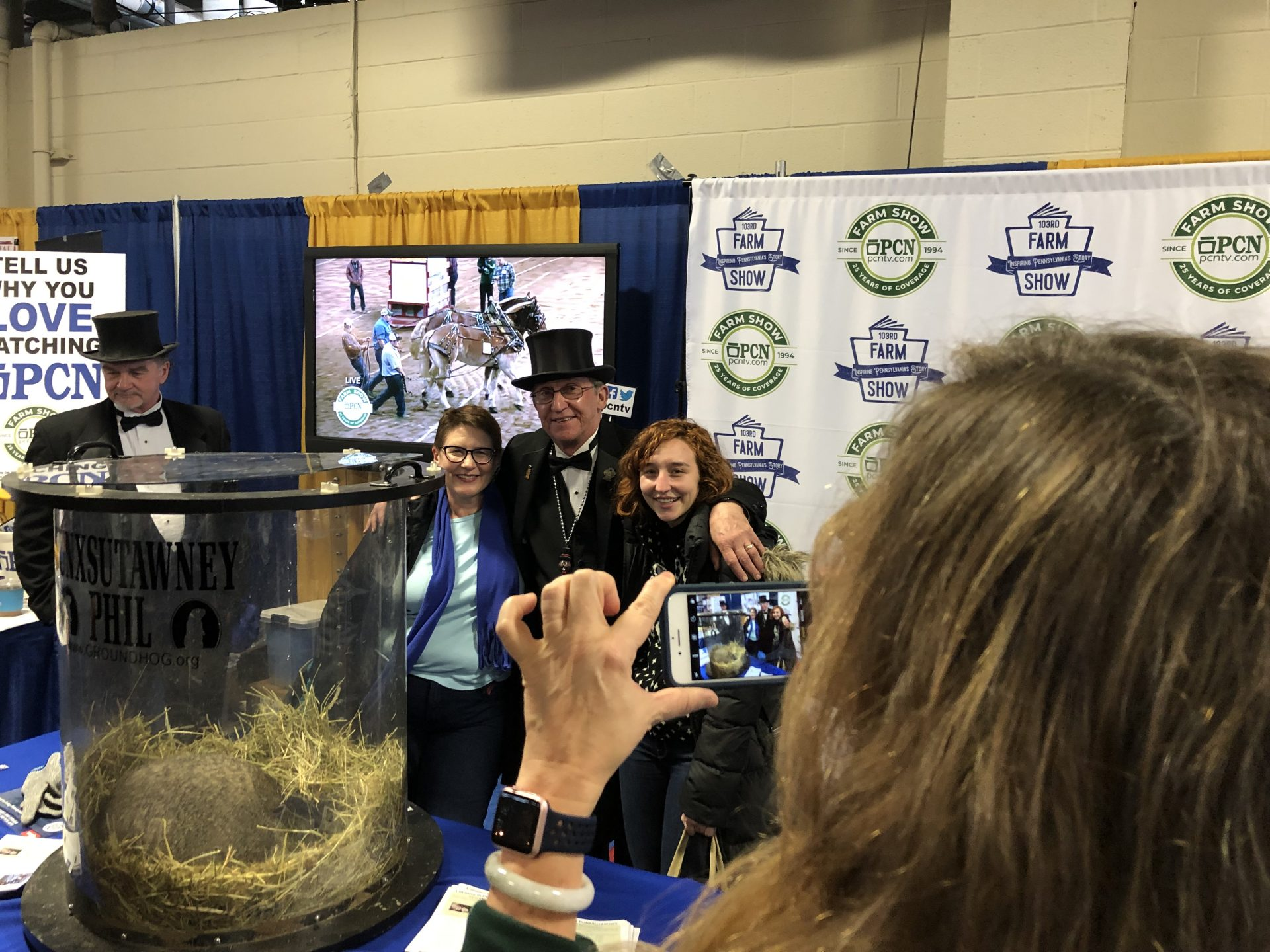 Visitors to the Pennsylvania Farm Show pose for a picture with a member of the Inner Circle and Punxsutawney Phil on Jan. 8, 2019.