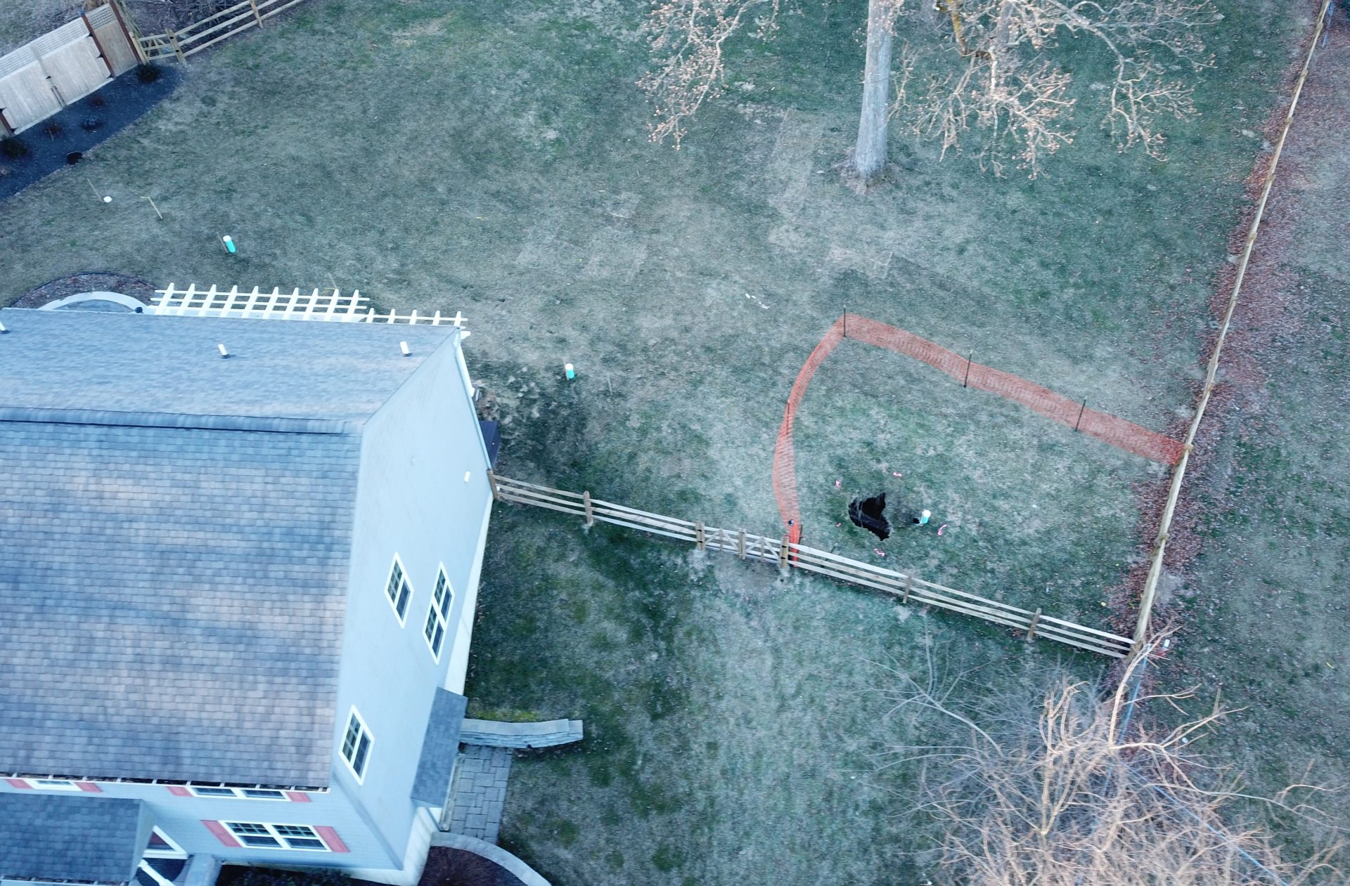 A sinkhole that opened up in January was surrounded by orange plastic fencing outside a suburban home at Lisa Drive in West Whiteland Township, Chester County.