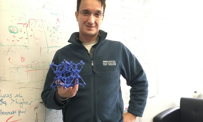 Chris Wilmer, assistant professor of chemical engineering at the University of Pittsburgh, holds a model of a metal organic framework.