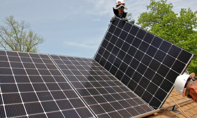 Patrick Whittaker of Solar States installs solar panels on the roof of a home in Bryn Mawr.