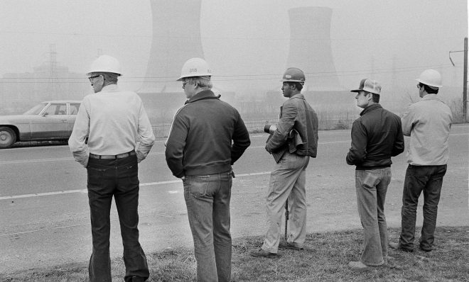 Workers from Metropolitan Edison's Three Mile Island nuclear plant stand outside visitors center early on March 30, 1979, as two cooling towers from the nuclear plant are visible in the background. Officials at the site declared an