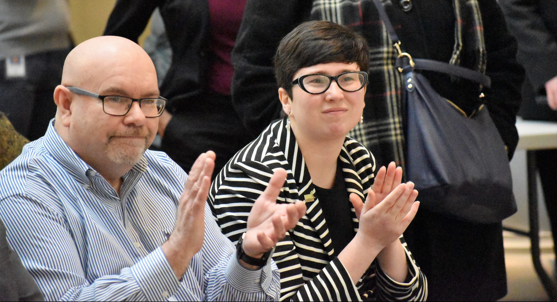 "Barry Loveland, curator for the exhibit, and Amanda L. Arbour, executive director of the LGBT Center of Central PA, applaud during a ceremony for ""The Long Road to LGBTQ+ Equality in Pennsylvania."" The ceremony was on March 18, 2019."