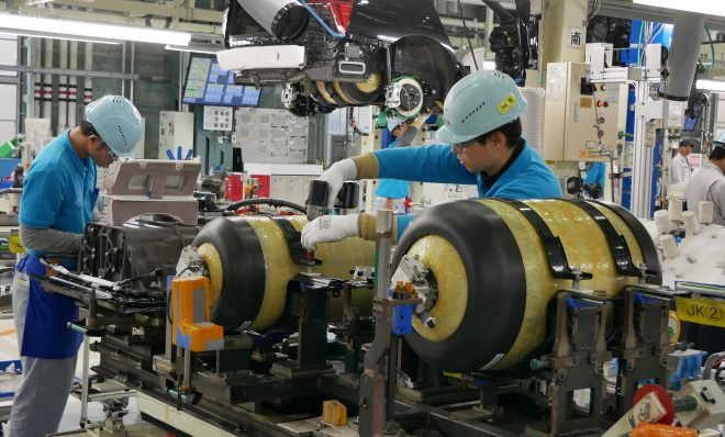 At Toyota's LFA Works factory in Japan, workers install hydrogen fuel tanks in a new Mirai.