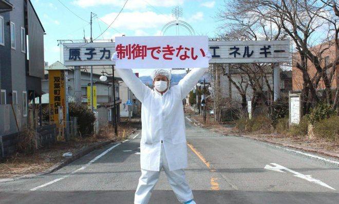 "As a boy, Yuji Onuma won a contest to create the town slogan for Futaba, Japan. His phrase -- ""Atomic power: energy for a bright future"" -- was enshrined on an archway over the town's main street. But after the Fukushima nuclear accident in 2011, Onuma -- like many in Japan -- has turned against what he used to champion. Here, he stands in front of the archway holding a banner that modifies his slogan as statements opposing nuclear energy."