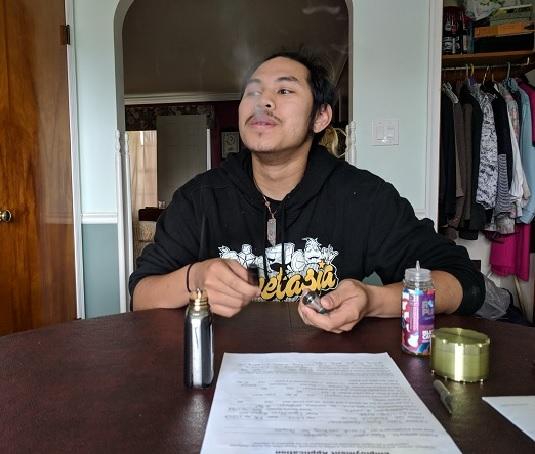 Quinton Tran, of Lancaster County, exhales vapor at his kitchen table.