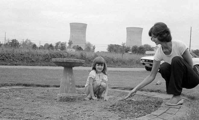 FILE PHOTO: Mrs. Joanne Noel, prepares her flower bed for planting in front of her Middletown, Pa., home as daughter Danielle, 4, watches as she sits on the ground, May 18, 1979. Noel evacuated her home with  her children during the crisis at Three Mile Island, seen in the background.