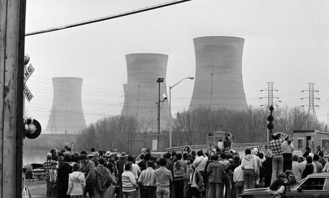 FILE PHOTO: Newsmen and spectators stand in front of the main gate of the Three Mile Island Nuclear Generating Station in Middletown, Penn., April 2, 1979.