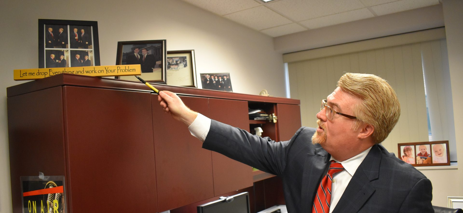Attorney Marc Scaringi points to photos of him with Republican President Donald Trump during an interview on April 25, 2019, in his Dauphin County office.