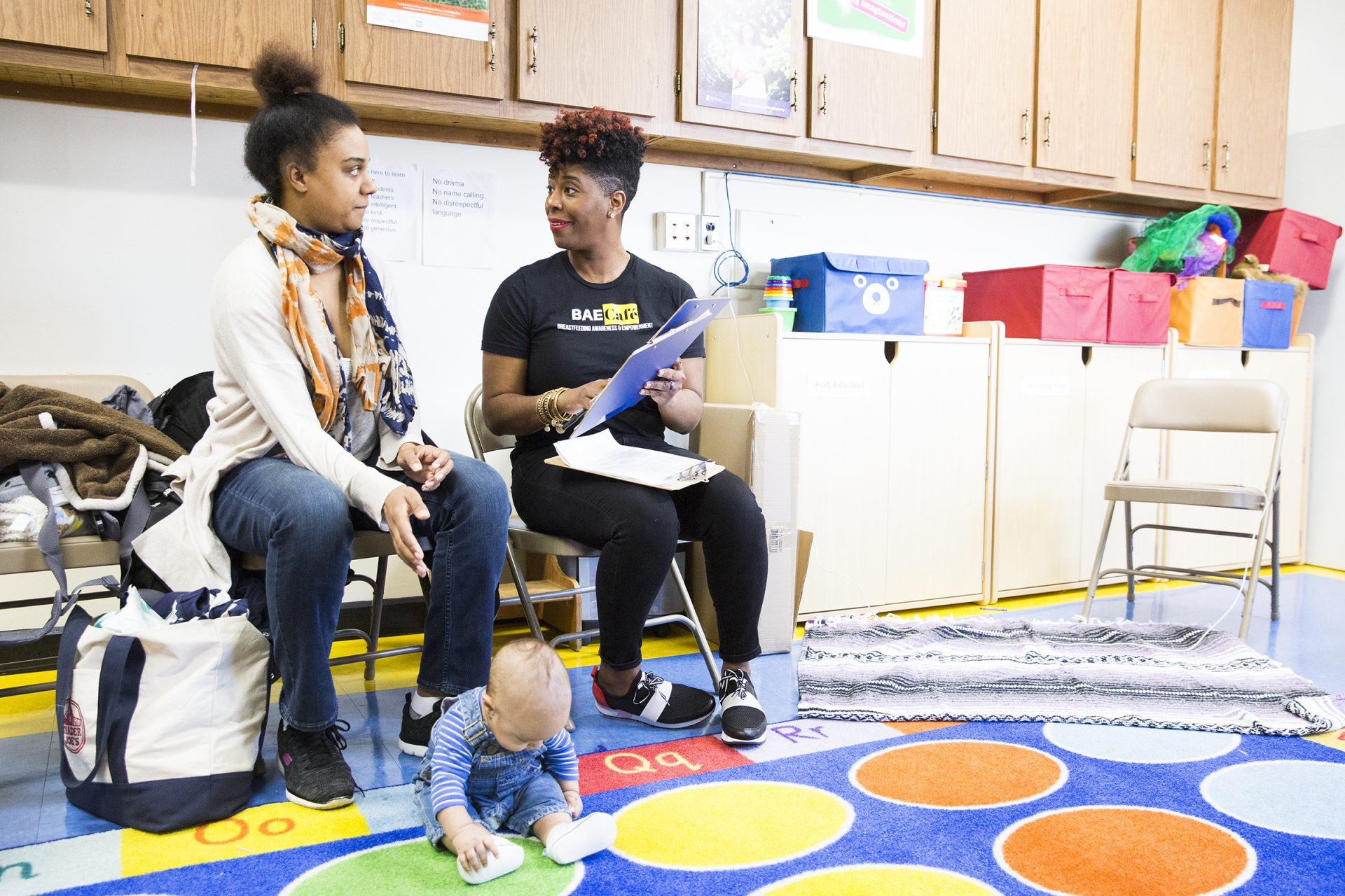 Jabina Coleman (right) introduces herself to Pamela Newman and 3-month-old James at the Lucien E. Blackwell library in Philadelphia. Coleman leads a breastfeeding class and co-runs the Prenatal Mental Health Alliance for Women of Color. In February, some mothers described experiencing postpartum depression.