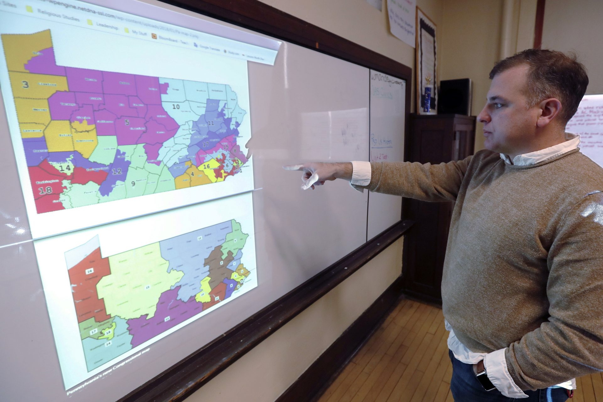 FILE PHOTO: William Marx, points to projected images of the old congressional districts of Pennsylvania on top, and the new re-drawn districts on the bottom, while standing in the classroom where he teaches civics in Pittsburgh on Friday, Nov. 16, 2018.