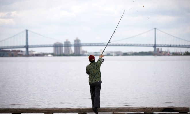 A man casts his line as he fishes for catfish in the Delaware River in view of the Benjamin Franklin Bridge, Thursday, May 19, 2016, in Philadelphia.