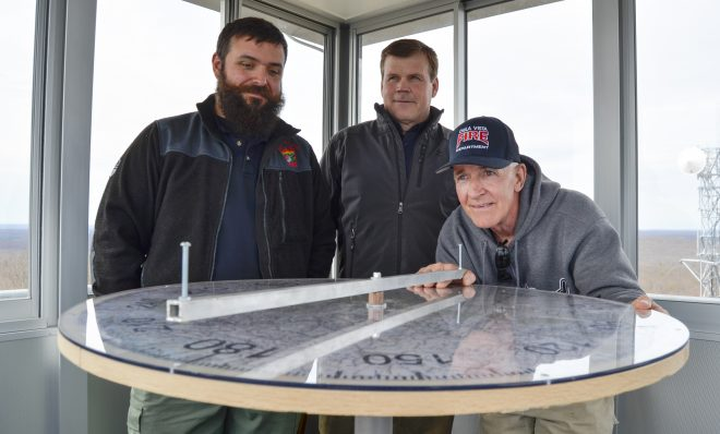 Officials from the Moshannon Forest District gather around the alidade, an instrument used to help personnel staffing lookout towers pinpoint the location of wildfires. From left to right, Joe Polaski, John Hecker and Larry Bickel stand in the new Chestnut Ridge tower.