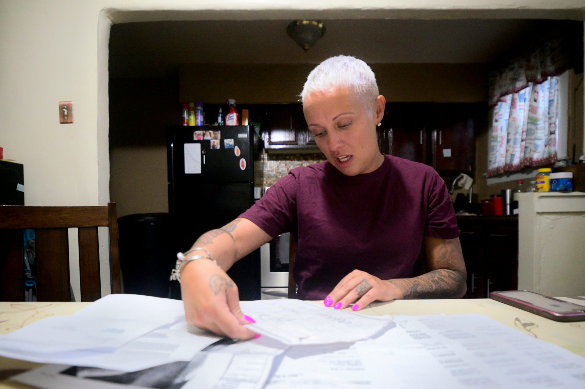 At the kitchen table last month, Summer Mills goes over documents accumulated in the past months while dealing with dental issues.