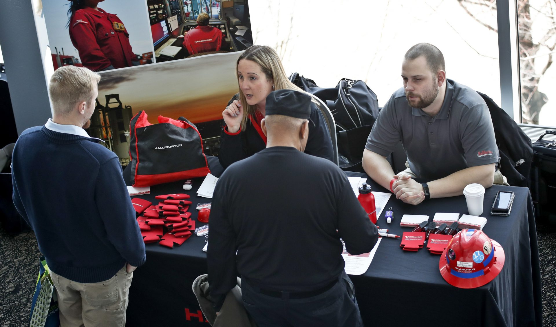 In this March 7, 2019, file photo, visitors to the Pittsburgh veterans job fair meet with recruiters at Heinz Field in Pittsburgh.