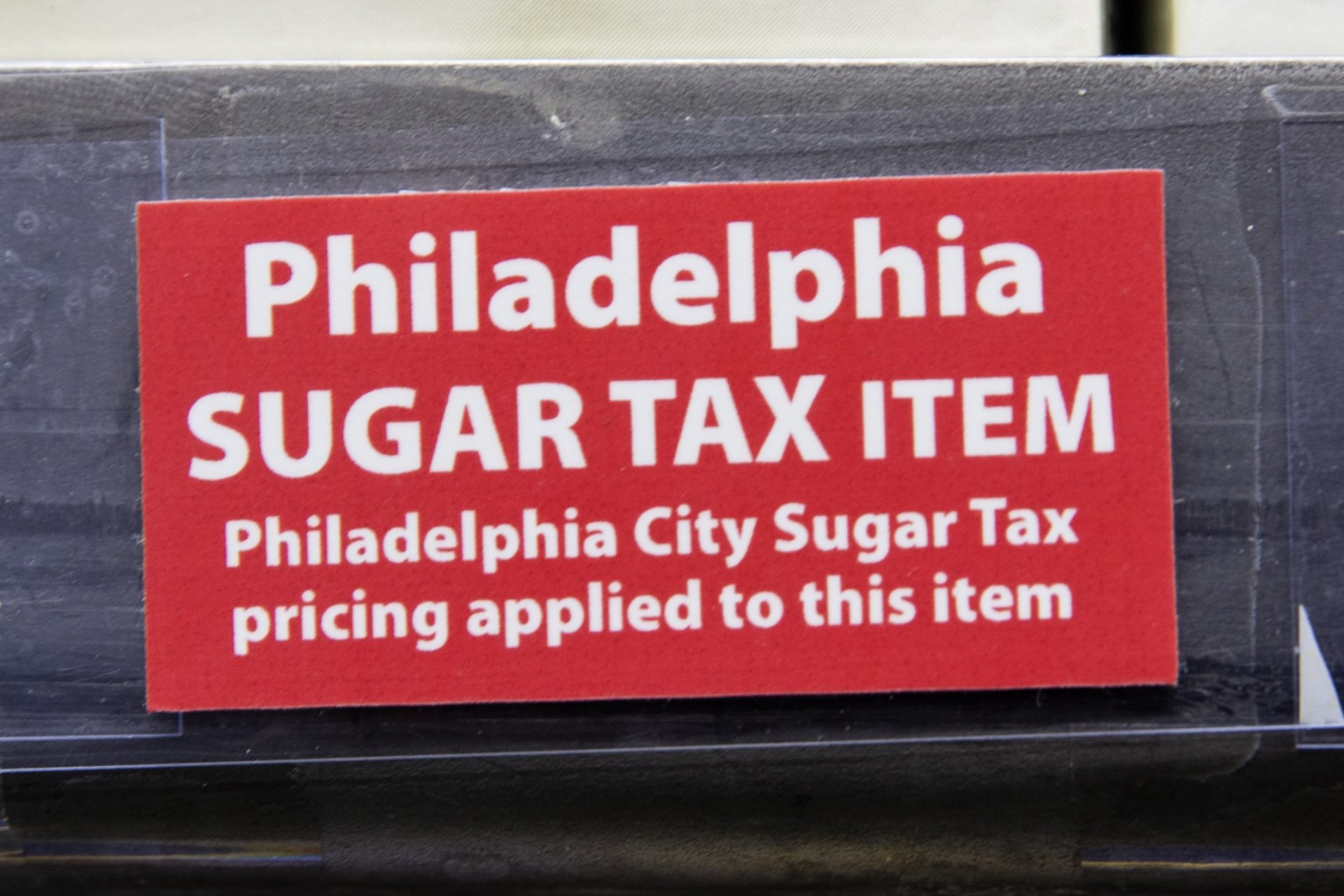 This March 16, 2017 photo shows a sticker alerting customers of the sugar tax posted by sweetened beverages at the IGA supermarket in the Port Richmond neighborhood of Philadelphia.