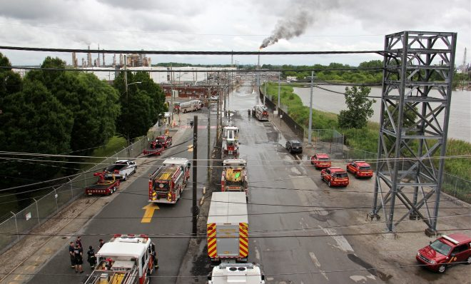 Philadelphia firefighters gather at the entrance to Philadelphia Energy Solutions Refinery, while a large flare burns off fuel to prevent it from feeding the massive fire at the refinery.