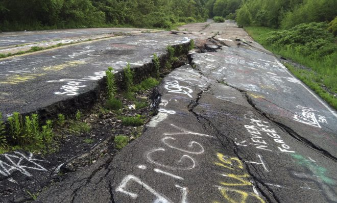 In this May 24, 2012 photo, Route 61 is shown eroded and covered in graffiti in Centralia, Pa. Fifty years ago a fire at the town dump spread to a network of coal mines underneath hundreds of homes and business in the northeastern Pennsylvania borough of Centralia, eventually forcing the demolition of nearly every building.