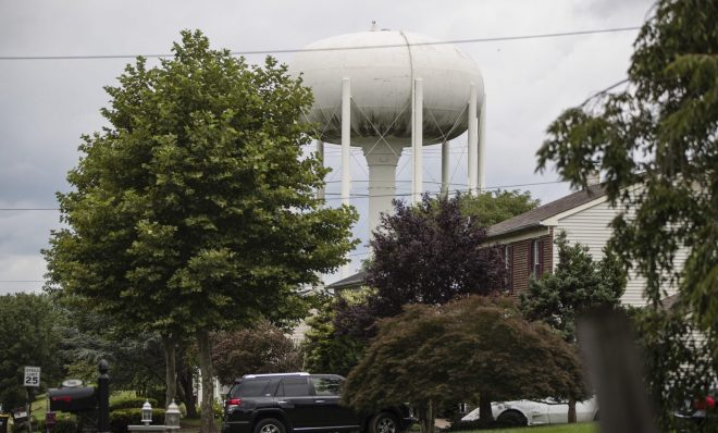 In this Aug. 1, 2018 photo, a water tower stands above a residential neighborhood in Horsham, Pa. In Horsham and surrounding towns in eastern Pennsylvania, and at other sites around the United States, the foams once used routinely in firefighting training at military bases contained per-and polyfluoroalkyl substances, or PFAS.