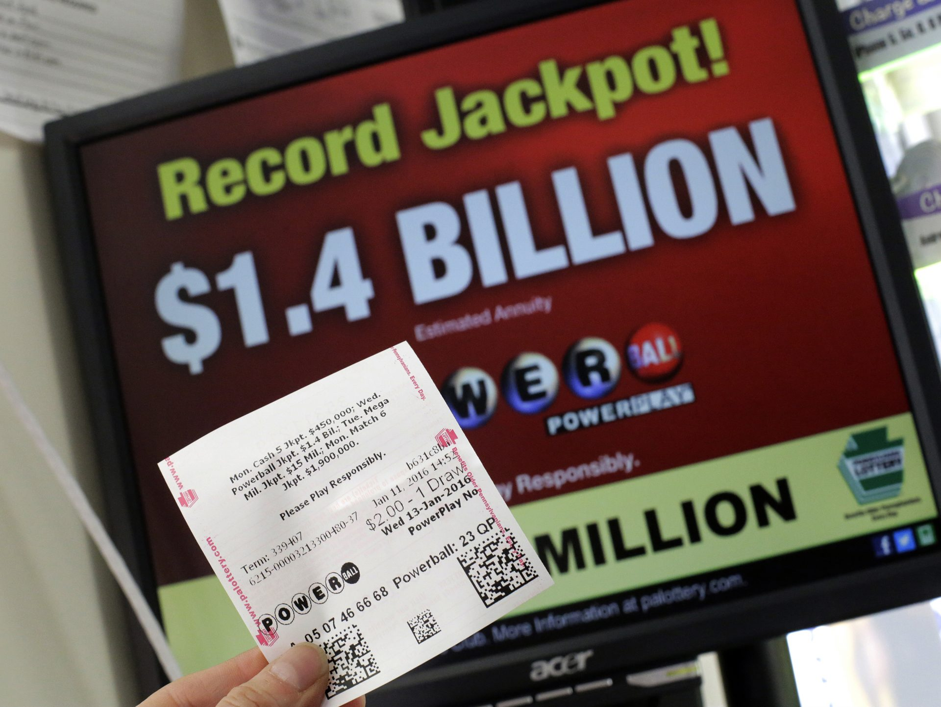 A Powerball ticket purchased in a convenience store in Lancaster, Pa., is held in front of a Pennsylvania Lottery computer screen advertising the record $1.4 billion Powerball jackpot, Jan. 11, 2015, in this file photo.