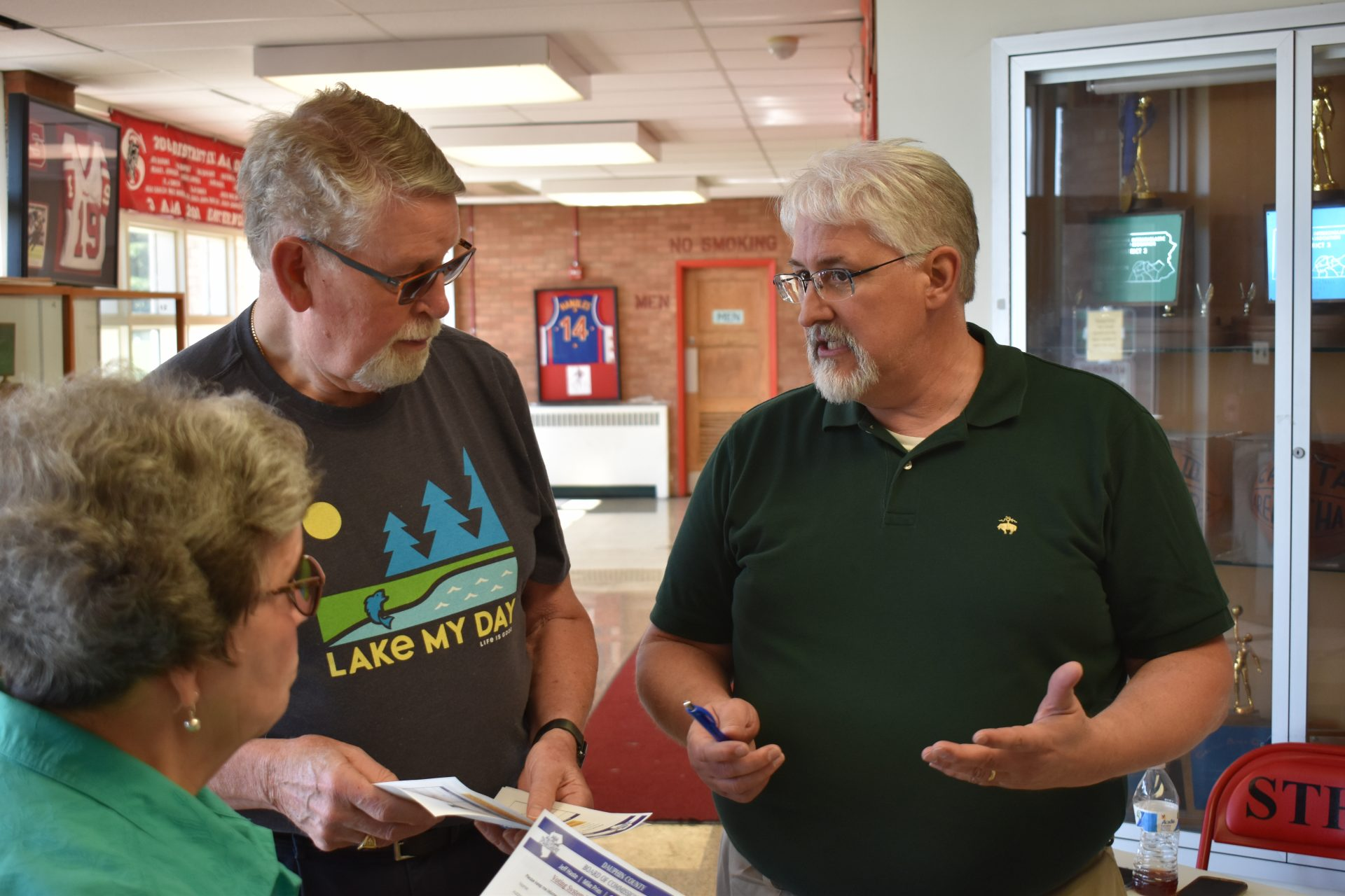 Jerry Feaser, director of elections and voter registration in Dauphin County, right, greets people at the start of voting machine demonstration on June 11, 2019, at Susquehanna Township High School.