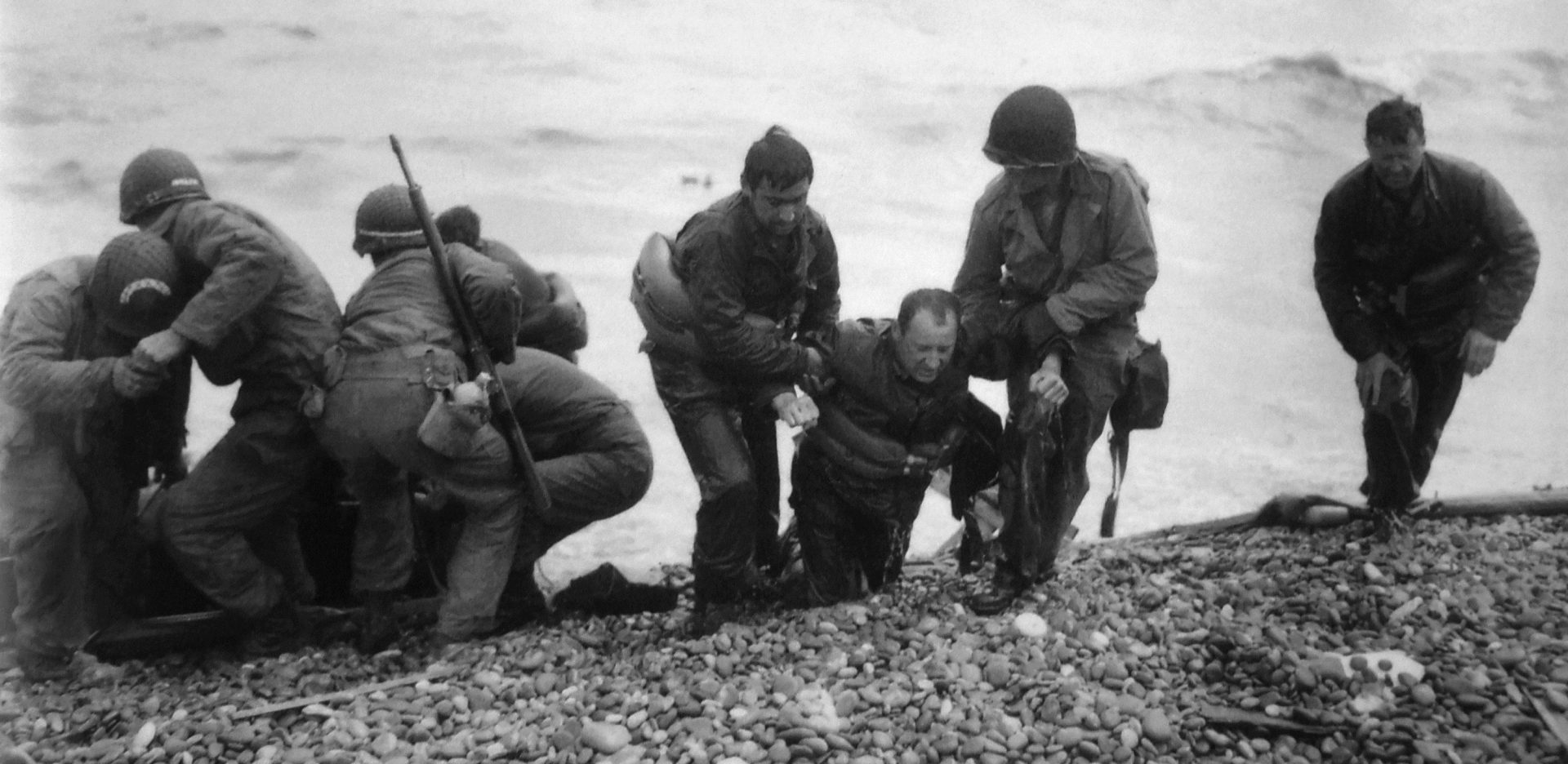 Members of an American landing unit help their exhausted comrades ashore during the Normandy invasion on June 7, 1944. Nick Russin is pictured in the center being dragged onto shore.
