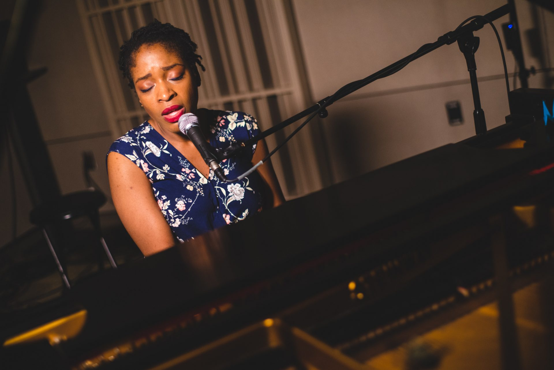 Joy Ike playing piano and singing