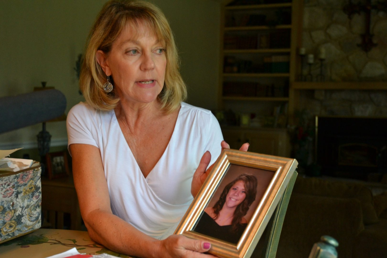 Martha Stringer holds a photo of her daughter, Kim, from when she was in high school. Kim is 27 now.
