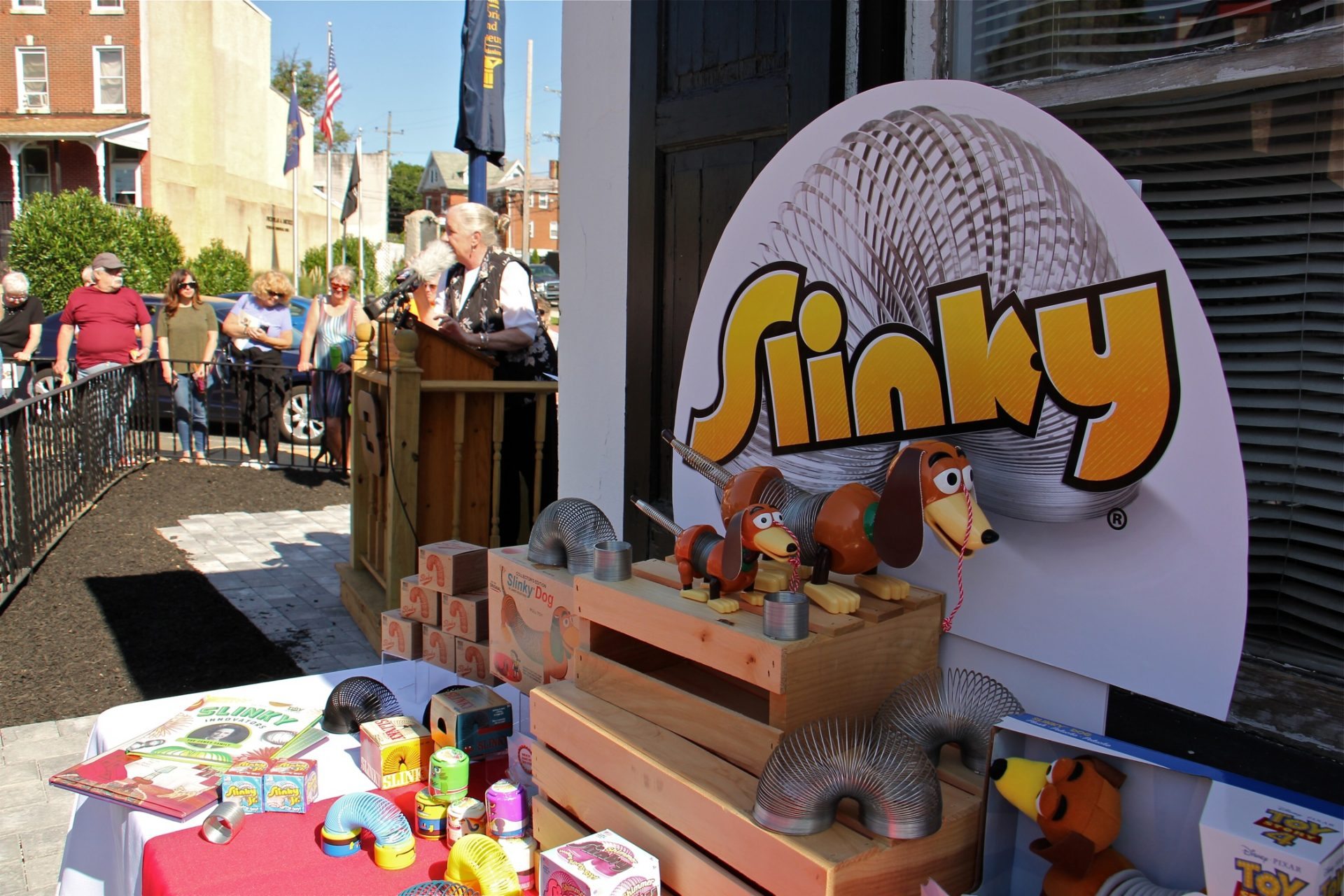 An array of Slinky toys are displayed outside the Clifton Heights Historical Society building, where a historical marker was placed identifying Clifton Heights as an early manufacturer of the popular toy.