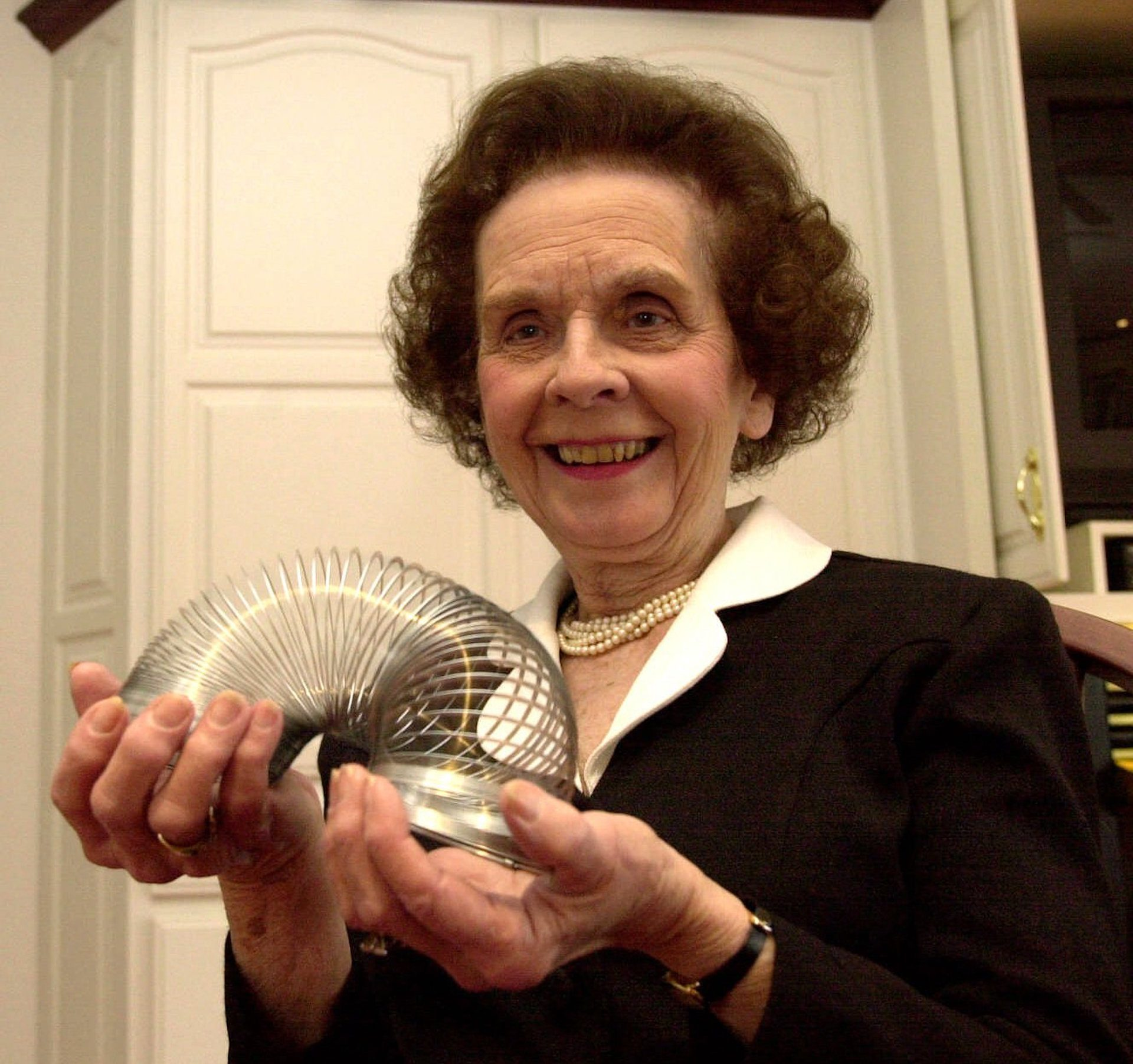 Betty James, retired president of James Industries, plays with a toy Slinky that made the family company famous on Thursday, Jan. 18, 2001, in Hollidaysburg, Pa. James will be inducted into the Toy Industry Hall of Fame next month. More than 250-thousand Slinkys have been sold since the founding of James Industries in 1945.