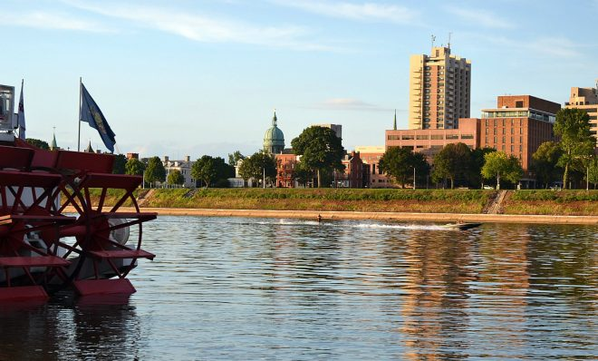 A man water-skis behind a boat on the Susquehanna River, as seen from City Island. In the foreground is the Pride of the Susquehanna boat. The state Capitol is visible across the river.