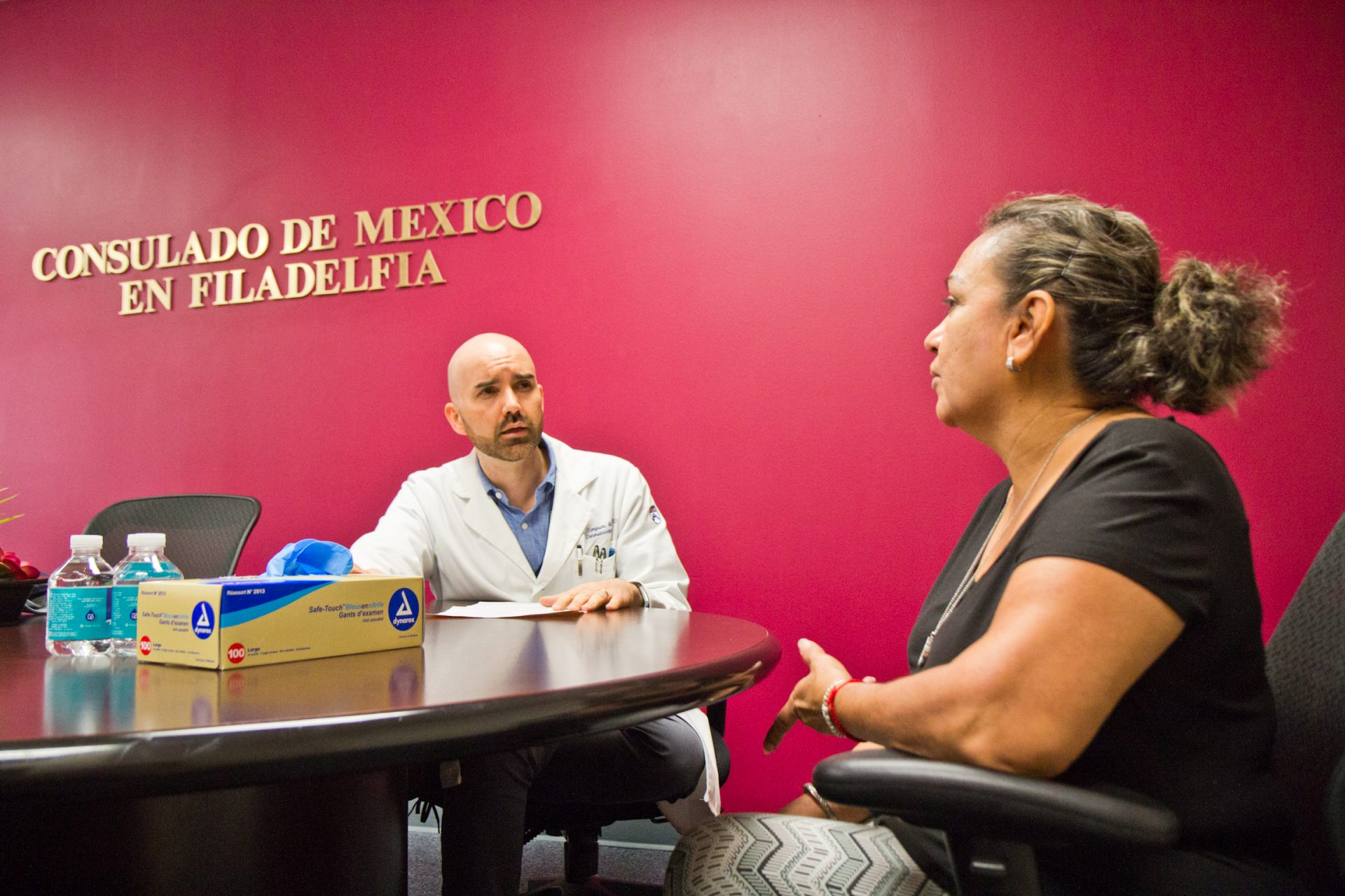 Dr. Corey Simpson, dermatologist, screens Diocelina Zabalo for skin cancer at Philadelphia's Mexican consulate.