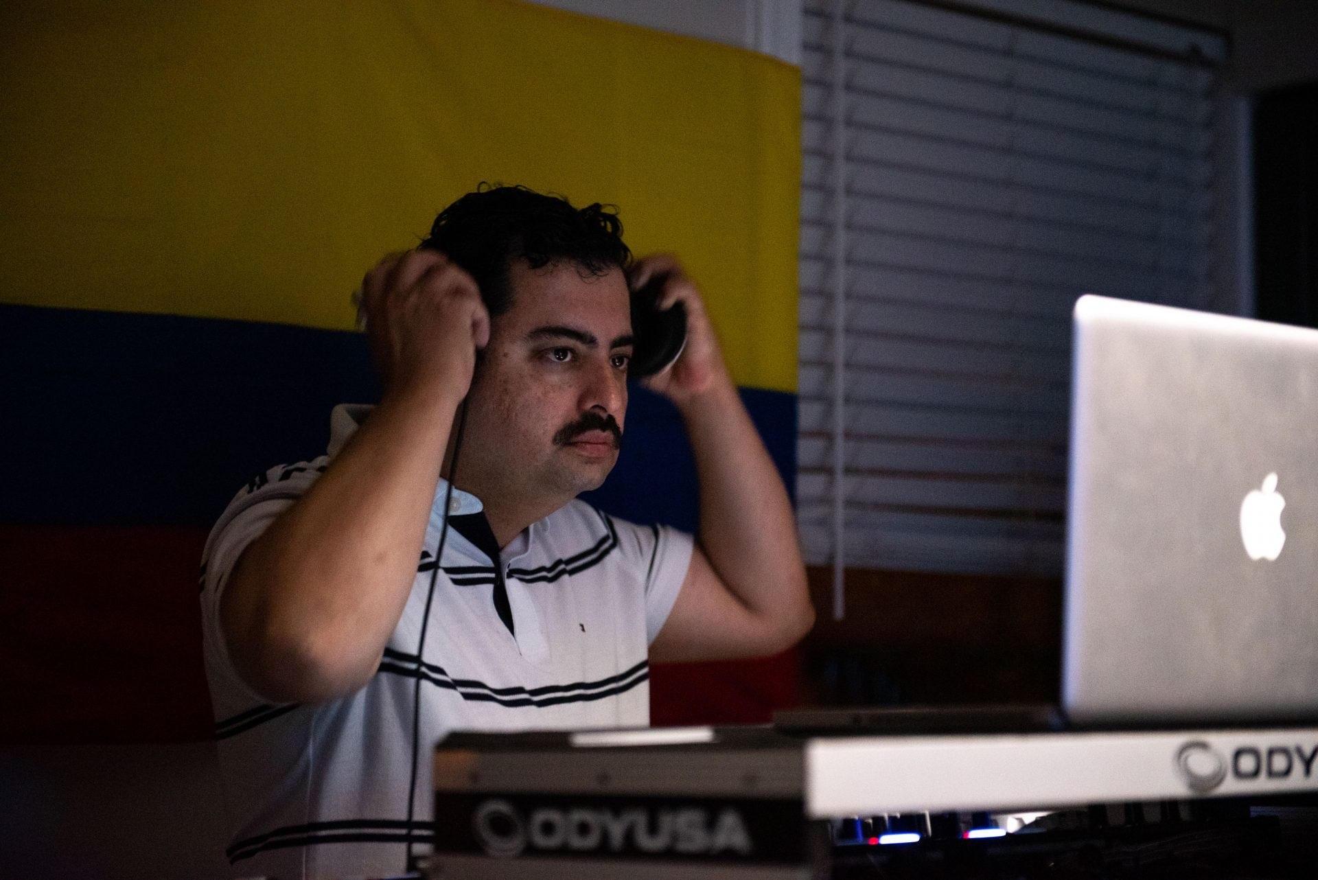 Jose Cardona, a Wilmington-area DJ, adjusts his headphones while keeping the music going during an at-home viejoteca in Oxford Circle on Saturday, September 14, 2019.